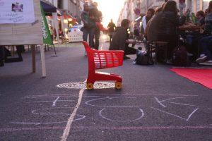 """Man sieht einen Spielzeugeinkaufwagen auf Louisenstraße. Davor sieht man """"FCK SUV"""""""
